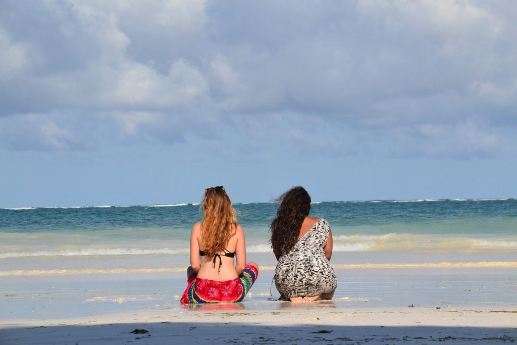 two girls sitting on the beach in Diani Beach