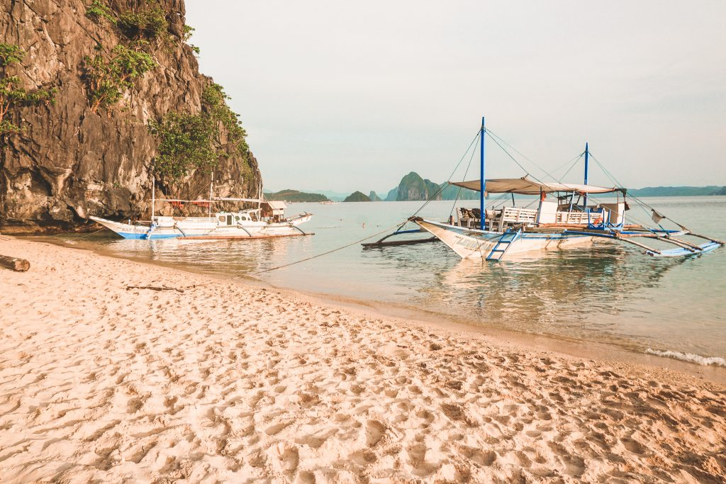 Boats in water on island in Philippines