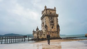 Woman walking in front of Tower of Belem